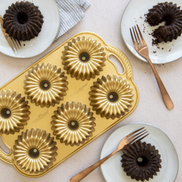Baked Brilliance Bundtlettes on white surface with chocolate cake and pan