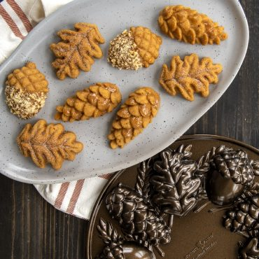 Baked leaf, acorn, and pinecone cakelets on a platter with pan on surface.