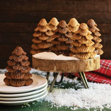 Baked tree cakes standing up on stand, snow holiday scene with plates next to cakes