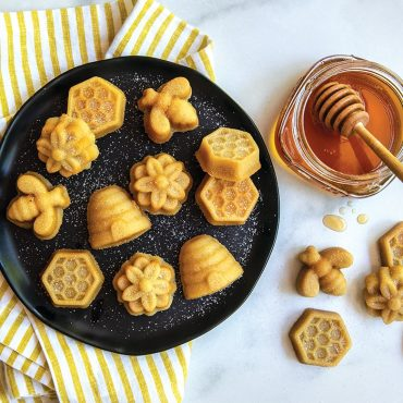 Baked bee bites on black plate, with jar of honey