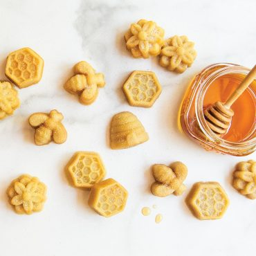 Baked bee bites on marble background with honey jar