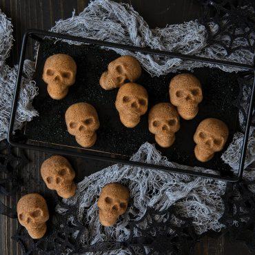 Baked mini skull cakes on platter with black sugar, Halloween props