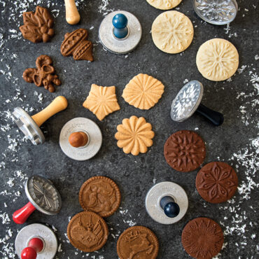 Cookie stamp group shot showcasing holiday baked cookies, cookie stamps on surface