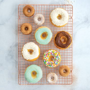 Assorted baked classic and mini donuts on cooling grid