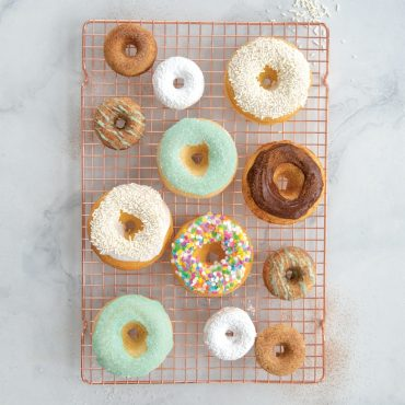 Assorted classic and mini baked donuts on cooling grid
