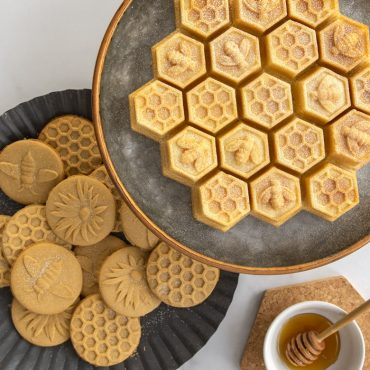 Baked honeybee stamped sugar cookies on plate with baked Honeycomb cake on cake platter- Bee Theme scene