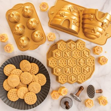Bee-themed bakeware group image, baked cookies on plate, cakes on surface and product
