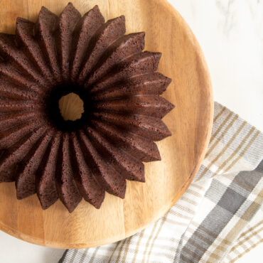 Baked chocolate Brilliance 5 Cup Bundt on wooden platter with towel.