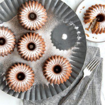 Sugared baked Brilliance Bundtlettes on cake pan, one cake on single plate