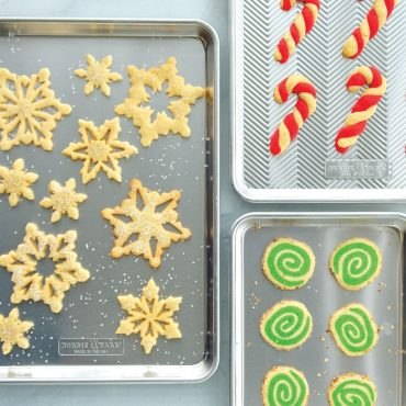 Variety of baked holiday cookies on sheet pans