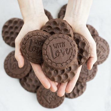 Baked chocolate stamped cookies in hand