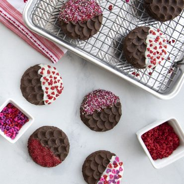 Baked stamped cookies dipped in white chocolate, sprinkles, baking sheet