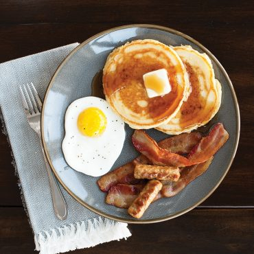 Pancakes, fried eggs, sausage, bacon on plate made on griddle