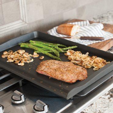 Grilled steak, onion, mushrooms, asparagus, on griddle on stovetop