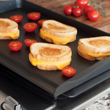 Grilled cheese sandwiches and grilled tomatoes on griddle on stovetop