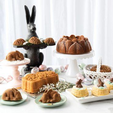 Easter baking display with baked bunny cakes, baked baskets, Bundt cake and floral loaf cake.