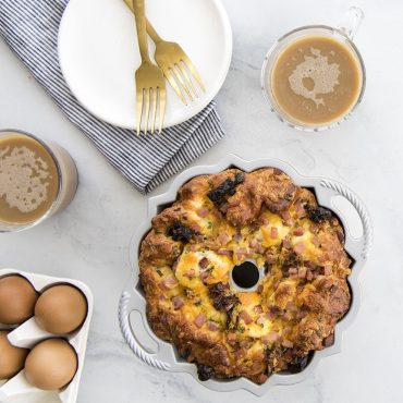 baked egg breakfast dish in cake pan with coffee in cups, fresh eggs