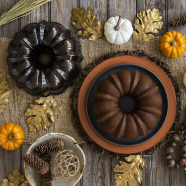 Fall table set up with Spice Bundt cake on platter and bronze pan next to it.