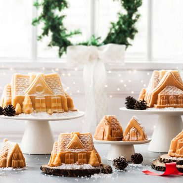 Various sized baked vanilla gingerbread house cakes on cake stands, dusted in powdered sugar