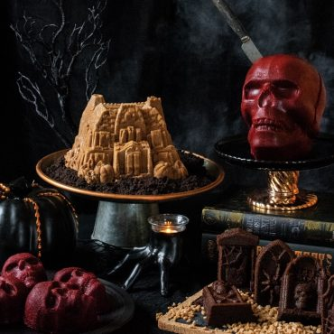 Various baked Halloween cakes on cake stands, Haunted Mansion, Skull Cakelettes, Tombstones , various Halloween decorations