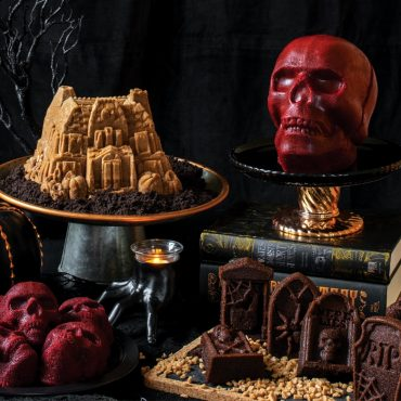 Various baked Halloween cakes on cake stands, Haunted Mansion, Skull Cakelets, Tombstones , various Halloween decorations