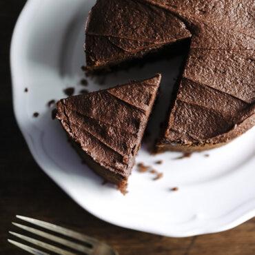Chocolate round cake on cake platter, one cut piece