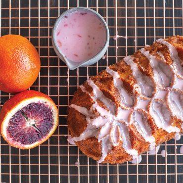 Baked blood orange Jubilee loaf cake with blood orange glaze, cut blood orange and whole orange on cooling rack, glaze pitcher