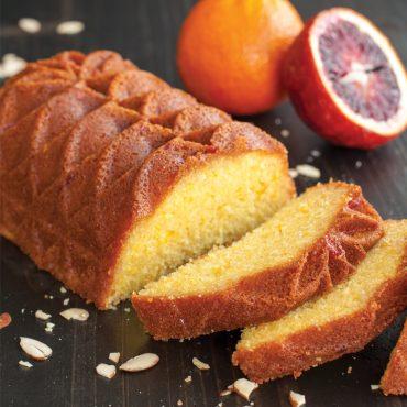 Baked blood orange Jubilee loaf cake cut into slices, cut blood orange and whole orange in background
