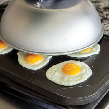 Stovetop cooking eggs on griddle with dome lid