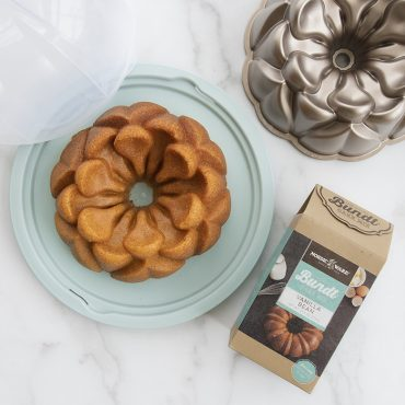 Baked Vanilla Bean Mix in Magnolia Bundt shape on cake keeper.