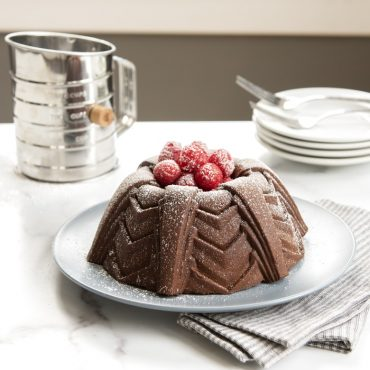 Baked chocolate Marquee Bundt with raspberries in the middle dusted with powdered sugar, plates in background.