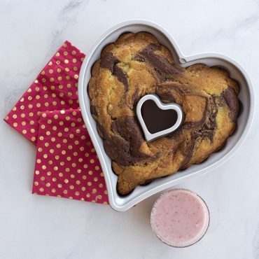 Baked marble cake in heart pan, bowl of berry glaze