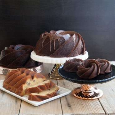 Four different version of Heritage cakes - baked chocolate cakes 10 cup, 6 cup, bundtlets, vanilla loaf with nuts, all on serving plates