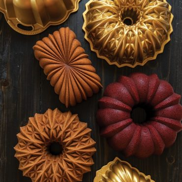 Group shot of baked Bundts and loaf cake with pans on surface