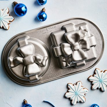 Pretty Presents Cake Pan on blue surface, decorations on surface