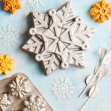 Snowflake cake pan on surface with snowflake cakelets in background.