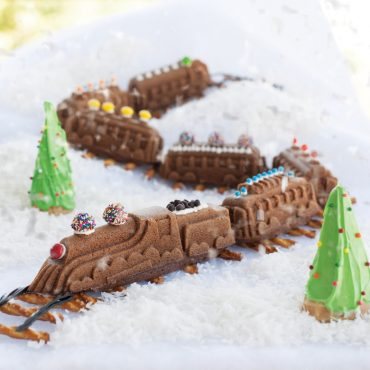 Baked Nordic Express Train cakes decorated with piped frosting and candies, on a pretzel train track and snow scene