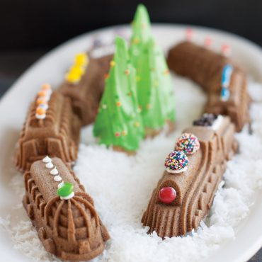 Baked Nordic Express Train cakes on an oval platter, all seven designs in a circle, decorated with snow and a frosted tree in the middle
