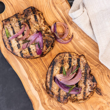 grilled pork chops from grill pan on wooden platter, topped with onions