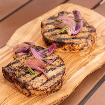 grilled pork chops on wooden board topped with onions and herbs
