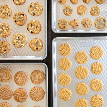 4 prim sheet pans with a variety of baked cookies