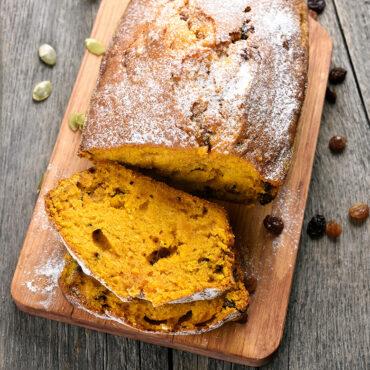Pumpkin quick bread on cutting board, one cut piece.