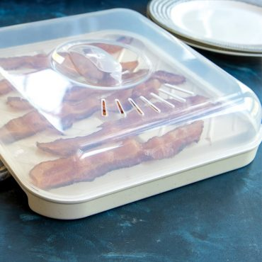 Angled closeup of microwaved cooked bacon on slanted tray with lid on top.