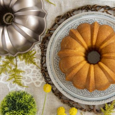 Plain baked lemon Bundt on platter, toffee pan next to it. Spring table scene