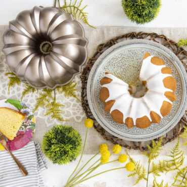 Baked Bundt with white glaze on platter, toffee pan on table with a slice of cake on a plate.