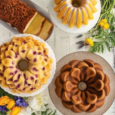 Variety of baked Bundt cakes and loaf cakes on serving plates, Blossom, Magnolia, Wildflower Loaf, Lotus
