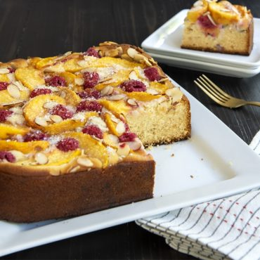 Baked peach and raspberry cake made in square springform pan, cut piece on plate in background.