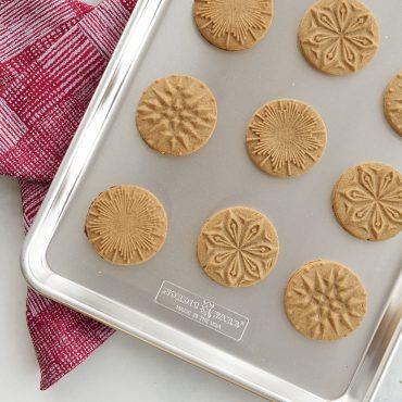 Baked gingerbread stamped starry night cookies on half sheet, towel