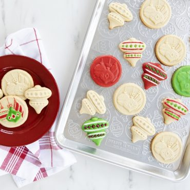 Baked cookie cut outs and holiday stamped cookies on ornament embossed baking sheet