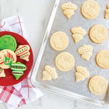 Baked holiday stamped cookies on ornament cookie sheet with a plate of decorated cookies